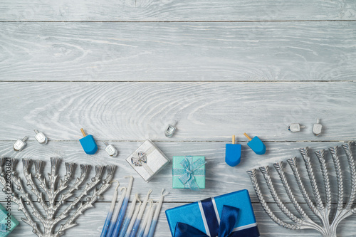 Jewish holiday Hanukkah background with menorah, spinning top and gift box on wooden table