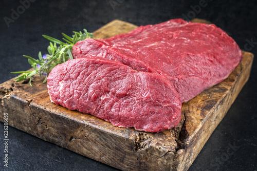 Foto op Aluminium Vlees Rohes Roastbeef vom Rind mit Kräutern angeboten als closeup auf einem alten Schneidebrett