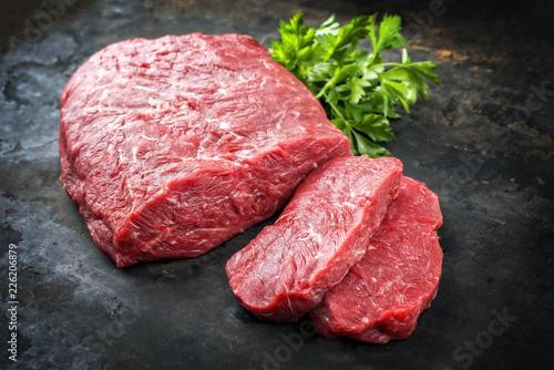 Rohes Rinder Roastbeef mit Kräuter angeboten als closeup auf einem alten rustikalen Metallblech