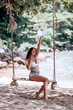 Young fit girl in denim shorts and a white bra swinging on a swing on the shore of the Andaman sea in Phuket.With his hand raised up. Happy