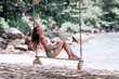 Young fit girl in denim shorts and a white bra swinging on a swing on the shore of the Andaman sea in Phuket. that the writes and reads in Notepad