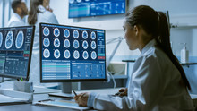 Female Medical Research Scientist Working With Brain Scans On Her Personal Computer, Writing Down Data In A Clipboard. Modern Laboratory Working On Neurophysiology, Science,  Neuropharmacology.