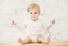 Adorable Blonde Baby Playing With Christmas Tree Lights