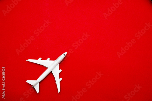 Valokuvatapetti Flat lay of miniature toy airplane on pastel red background minimal trip and travel creative concepts