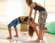 Yoga Teacher Helps Student In ...