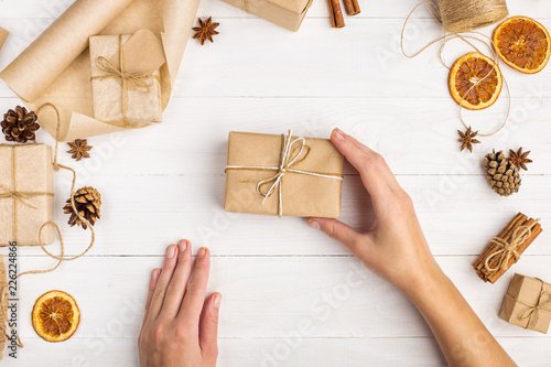Women's hands hold a gift of craft paper  Against the