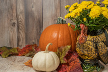 Thanksgiving Decor With Orange And White Pumpkins And Yellow Chrysanthemums In A Turkey Shaped Vase With Rustic Wood Background