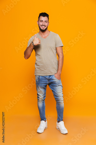 Full length portrait of a smiling young casual man Wall mural