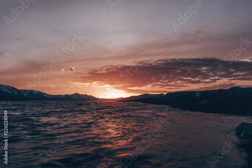 Foto op Aluminium Zalm Beautiful landscape with high rocks with illuminated peaks, stones in mountain lake, red sky and yellow sunlight in sunrise. Mongolia. Amazing scene with Altay mountains.