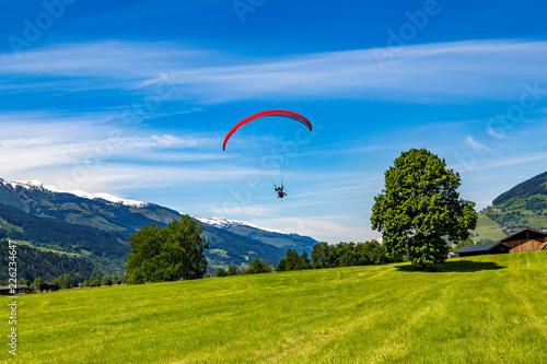 ein Gleitschirmflieger will auf einer Wiese landen, im Hintergrund Berge