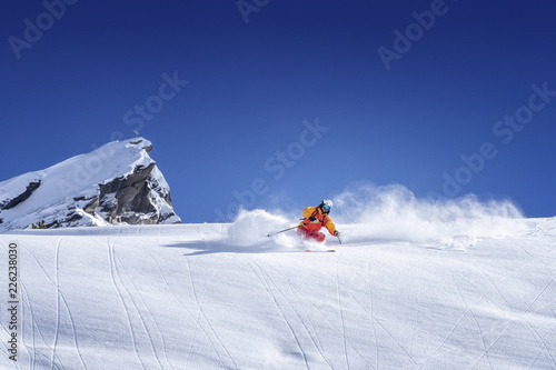 Fotografía  Skier skiing downhill in high mountains against blue sky