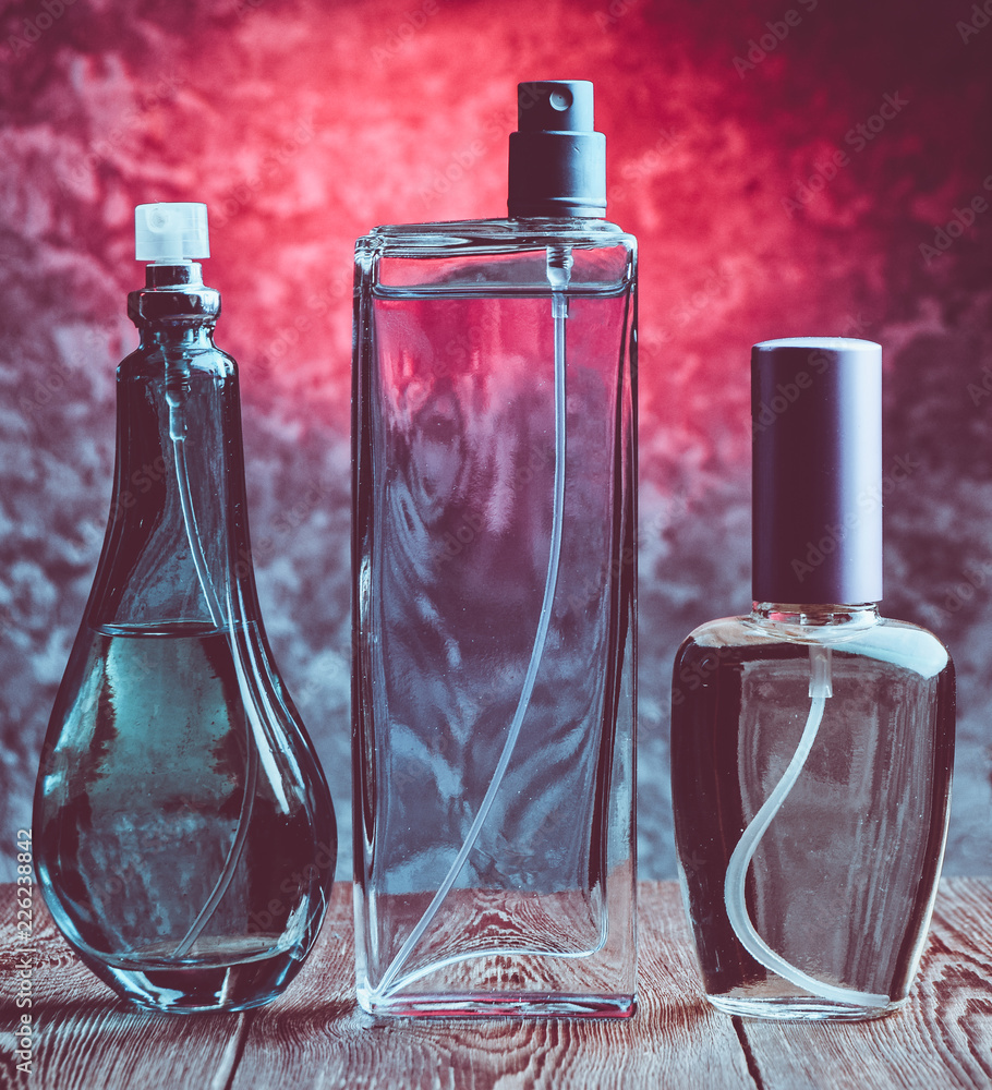 Fototapety, obrazy: Three different bottles of perfume on a wooden shelf against the background of a concrete wall. Women's accessories for attractiveness. Inviting scent.