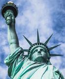 Fototapeta Nowy Jork - Estatua de la libertad, vista desde un ángulo bajo, con fondo nublado y cielo azul, en la Isla de la Libertad de Nueva York, EE. UU.,