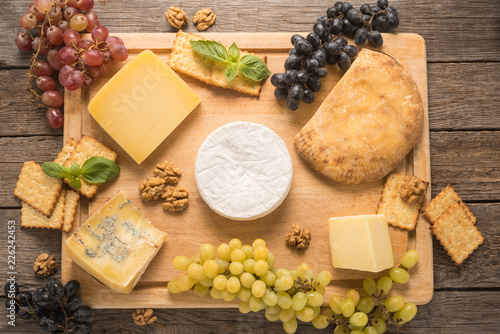 Cheese with grapes, walnuts and cracker on a table