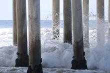 Waves Crashing On To Pier Pilings Under The Huntington Beach Pier