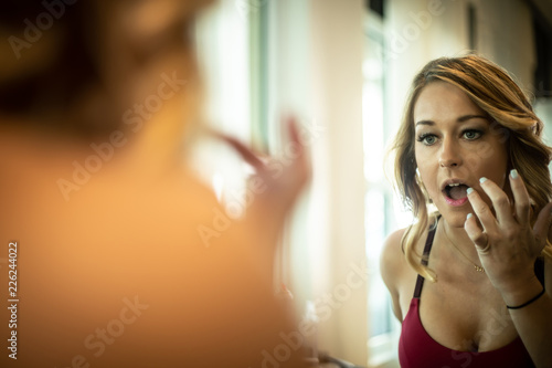 Gorgeous Woman Applying Lipstick In The Mirror Canvas Print