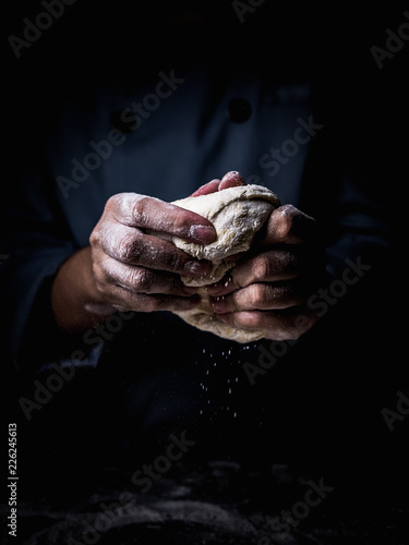 Canvas Prints Bread pastry chef hand kneading Raw Dough with sprinkling white flour over kitchen table.