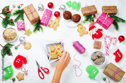 Christmas background with gifts, cookies, Christmas decoration and woman's hands