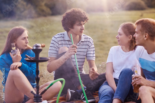 Photo  Shot of happy classmates smoke hookah, look at curly guy who tells interesting story, drink beverage, have picnic together, enjoy calm peaceful atmosphere in countryside