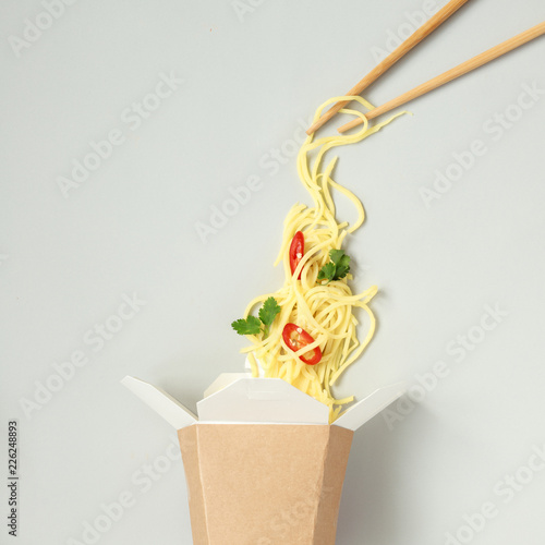 Asian food with chopsticks. Asian egg noodles with chili and cilantro in take away paper box, top view