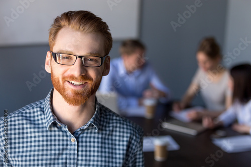 Fotografia  Smiling red-haired millennial business man in glasses looking at camera posing a