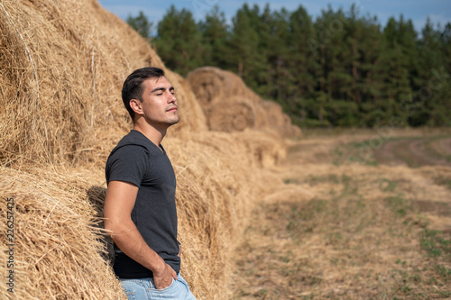 Fotografie, Obraz  A young man in a gray t-shirt and jeans stands at a haystack, breathing clean ai