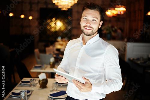 Papiers peints Restaurant Smiling man with tablet in restaurant