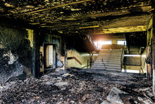 Burned Interiors After Fire In Industrial Or Office Building. Walls And Staircase In Black Soot