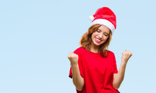 Young Beautiful Woman Over Isolated Background Wearing Christmas Hat Very Happy And Excited Doing Winner Gesture With Arms Raised, Smiling And Screaming For Success. Celebration Concept.
