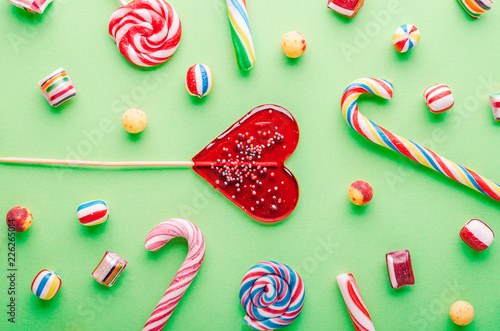 Fototapety, obrazy: Candies and lollipops on a green background