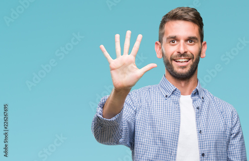 Photographie  Young handsome man wearing white t-shirt over isolated background showing and pointing up with fingers number five while smiling confident and happy