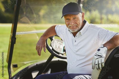 Foto Senior man smiling while sitting in a golf cart