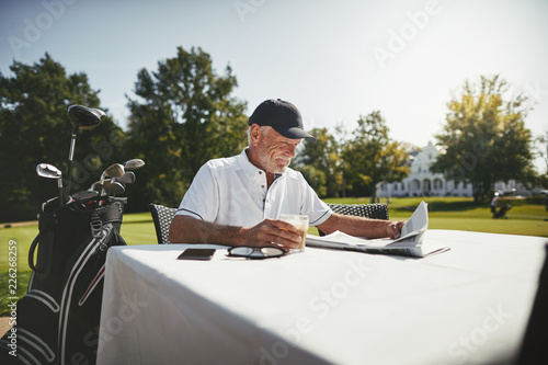 Fotografie, Obraz  Senior man relaxing with coffee at his golf clubhouse