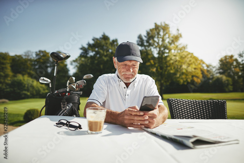 Fotografie, Obraz  Senior man using a cellphone at his golf club restaurant