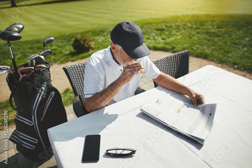 Photo Senior man sitting with coffee at his golf club restaurant