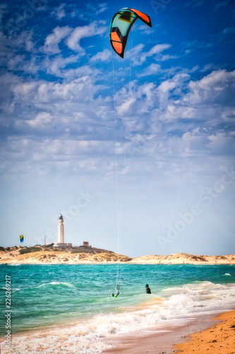 Surfers on the beach of Los Canos de Meca, with the Trafalgar lighthouse in the background, in southern Spain
