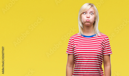 Valokuvatapetti Young beautiful blonde woman over isolated background puffing cheeks with funny face