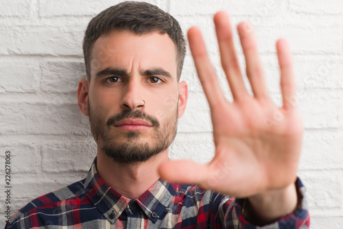 Fotografija  Young adult man standing over white brick wall with open hand doing stop sign wi