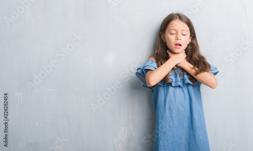 Young hispanic kid over grunge grey wall shouting and suffocate because painful strangle Wallpaper Mural