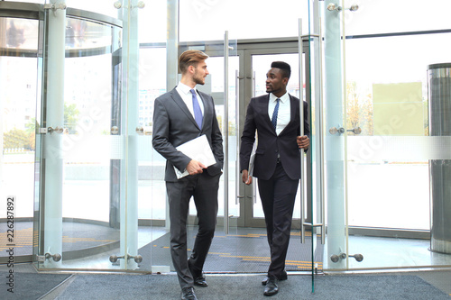 Fényképezés  Two multinational young businessmen entering in office building with glass doors