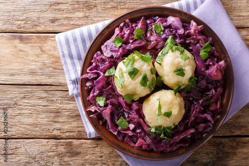 German food knodel potato dumplings and stewed red cabbage close-up on a plate. Horizontal top view from above