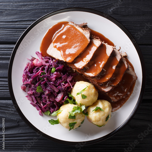 German Slow Cooker Pot Roast (Sauerbraten) with potato dumplings and red cabbage close-up. top view from above