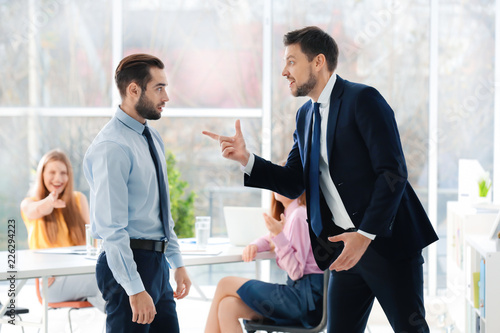 Fototapeta Young man bullying his colleague at work obraz