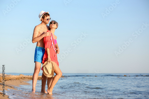 Poster Artist KB Happy young couple near water on beach. Space for text