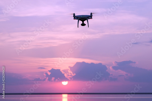 Silhouette of a drone at sunrise over the lake against the sky with the rising sun. Quadcopter, clouds, morning sunlight. Aerial photo and video. Copy space.