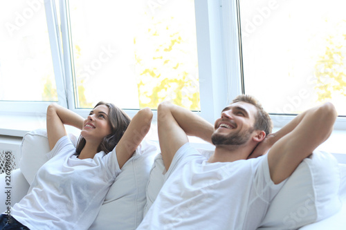 Smiling beautiful couple sitting on a sofa and dreaming about new home Canvas-taulu