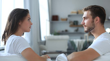 Side View Of A Couple Talking Sitting On A Couch And Looking Each Other At Home.