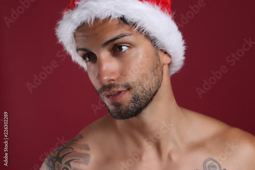 Fotografía  Sexy man in santa hat on red background