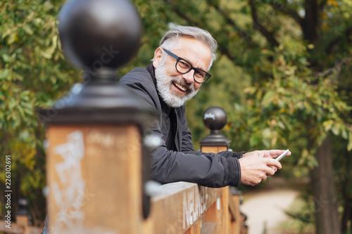 mann lehnt draußen auf einem holzgeländer und hält sein handy in der hand Fototapete