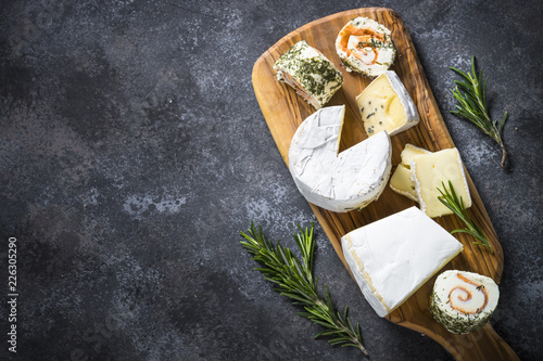 Fototapeta Cheese platter on dark stone table. obraz